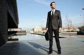 Portrait of a handsome young business man standing in the street — Stock Photo