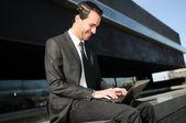 Un uomo d'affari, seduta sul pavimento con un computer portatile — Foto Stock