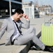 Man dressed in suit and suitcase sitting on the floor in the str — Stock Photo
