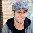 Stock Photo: Portrait of handsome man in urban background wearing a retro cap