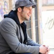 Portrait of handsome man in urban background wearing a retro cap — Stock Photo