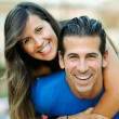 Smiling young man piggybacking his pretty girlfriend - Stock Photo