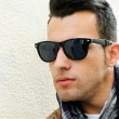 Stock Photo: Attractive mwearing tinted sunglasses in urbbackground