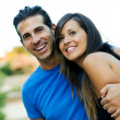 Portrait of a beautiful young couple smiling together - Stock Photo