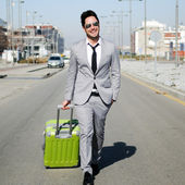 Man dressed in suit and suitcase walking along the street — Stock Photo