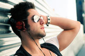 Portrait of handsome man in urban background listening to the mu — Stok fotoğraf