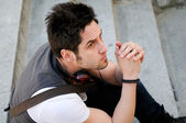 Portrait of young pensive man sitting on steps, with headphones — Stock Photo