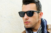 Attractive man wearing tinted sunglasses in urban background — Stock Photo