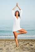Pretty woman doing yoga on the beach — Stock Photo
