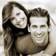 Portrait of smiling young man piggybacking his pretty girlfriend in the park  — Photo