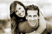 Portrait of smiling young man piggybacking his pretty girlfriend in the park — Stock Photo