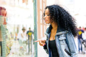 Portrait of an attractive black woman, afro hairstyle, looking at the shop window — Stock Photo