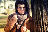 Attractive young handsome man, model of fashion in a park — Stock Photo