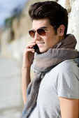 Handsome man in urban background talking on phone — Stock Photo
