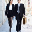 Attractive business walking on the street. Couple working - Stock Photo