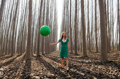 Beautiful blonde girl, dressed in green, walking into the forest — Stock Photo