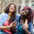 Two beautiful girls in urban backgrund, black and mixed women — Stock Photo