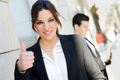 Attractive businesswoman showing thumb up sign — Stock Photo