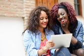 Two beautiful girls with tablet computer in urban backgrund — Stock Photo