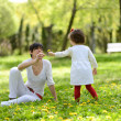 Mother and little girl playing in the park - Stock Photo