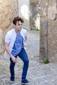 Aantrekkelijke jonge man in stedelijke achtergrond — Stockfoto