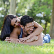 Happy smiling couple laying on green grass - Stock Photo