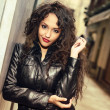 Attractive black woman in urban background wearing leather jacke — Stock Photo
