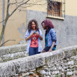 Stok fotoğraf: Happy young girls taking pictures of themselves through cellphon