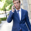 Attractive young businessman on the phone in urban background — Stock Photo