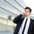 Attractive young businessman on the phone in an office building — Stock Photo