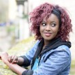Beautiful black woman in urban background with red hair — 图库照片