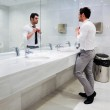 Man getting dressed in a public restroom with mirror — Stock Photo