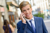 Attractive young businessman in urban background — Stock Photo