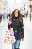 Attractive young woman with shopping bags in a commercial street — Stock Photo