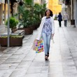 Beautiful woman with shopping bags walking along a commercial st — Stock Photo #38690393