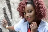 Beautiful black woman in urban background with red hair — Stock Photo