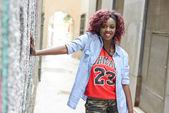 Krásná černoška v městské pozadí s červenými vlasy — Stock fotografie