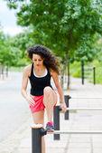 Jeune femme souriante joyeuse dans les sports wear en contexte urbain — Photo