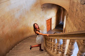 Attractive smiling blonde woman on stairs — Stock Photo
