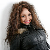 Attractive mixed woman on white background wearing leather jacke — Stock Photo