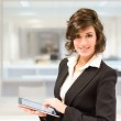 Young pretty business woman with tablet computer in the office — Stock Photo #42983815