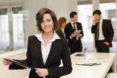 Бизнес-лидер, глядя на камеру в рабочей среде — Стоковое фото