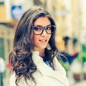 Göz gözlük kentsel arka planda gülümseyen güzel kadın — Stok fotoğraf