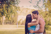 Young couple kissing in a beautiful park — Stock Photo
