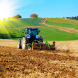 Stock Photo: Tractor plows field in spring, with sunlight
