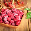 Frozen raspberries in the wooden bowl — Stock Photo