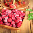 Frozen raspberries in the wooden bowl — Stock Photo #19442419