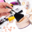 Powder with cosmetic brush, on table wit makeup - Stock Photo