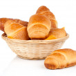 Fresh and tasty croissant in a straw basket, isolated on the white background — Stock Photo