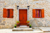 House with wooden windows and doors, surrounded in the stone wall. with flowers at the door — Stock Photo